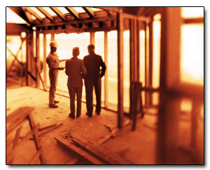 ist2_7828848-couple-talking-to-construction-worker-in-framework-of-house